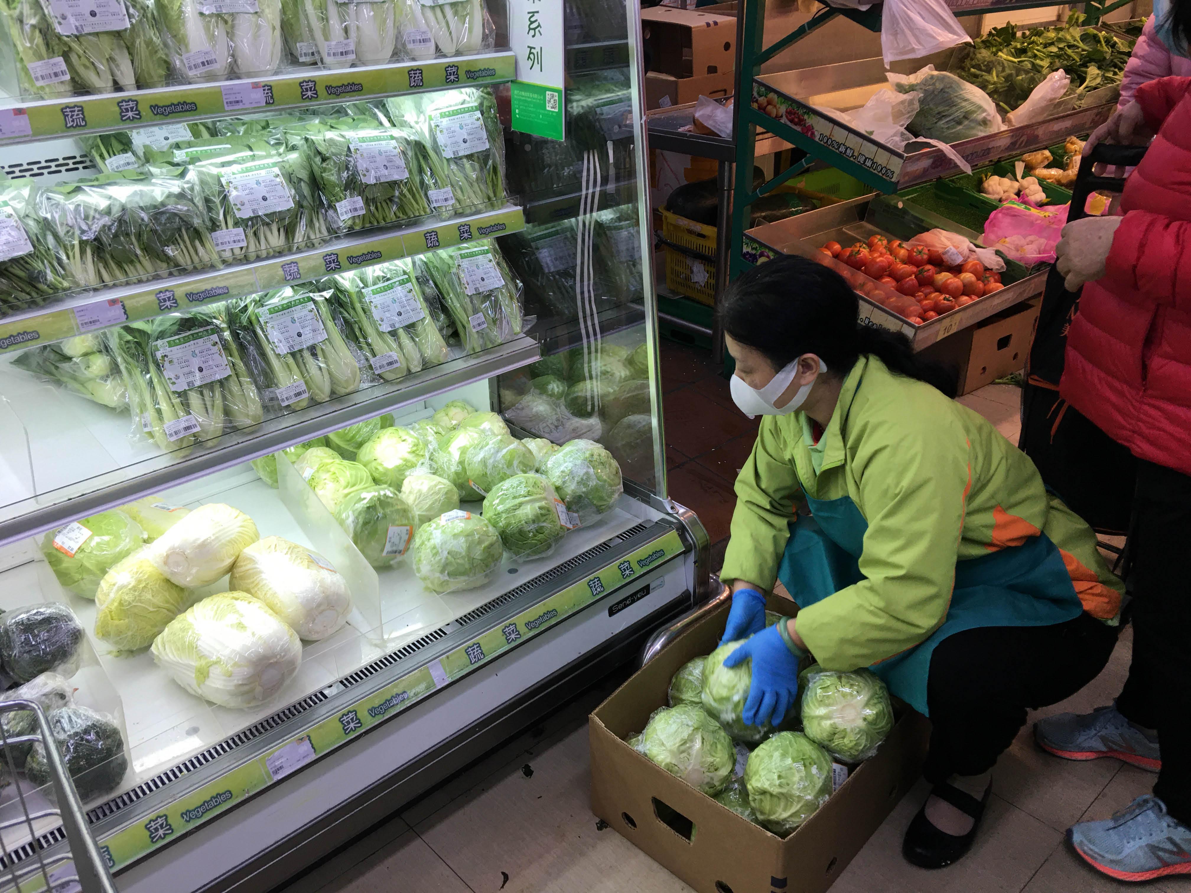超市員工將蔬菜上架.jpg